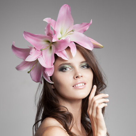 lily flowers: Beautiful Woman With Flowers Wreath In Her Hair. Pink Lily. Stock Photo