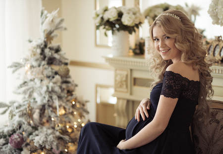 parentage: Beautiful Pregnant Woman In A Holiday Dress. Christmas Tree Background.