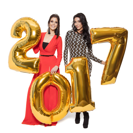 marry christmas: Charming Women Holding Big Golden Numbers 2017. Happy New Year. Marry Christmas. Isolated. Stock Photo