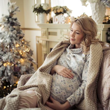 navidad elegante: Hermosa mujer embarazada en ropa cómodas. Sentado en una silla cerca de la árbol de Navidad.
