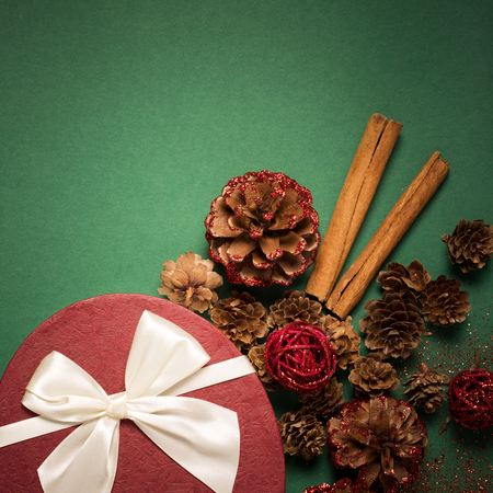 packaging box: Christmas gift box and decorations on green paper background. Top view with copy space
