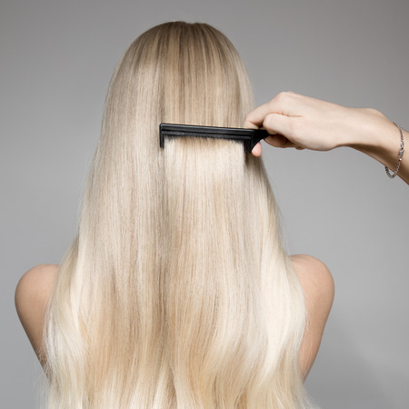 Back View Portrait Of A Beautiful Blond Woman With Long Hair. Hand hairdresser with hairbrush.