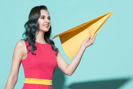 yellow paper: Portrait of a beautiful woman holding a yellow paper airplane. On a blue background.