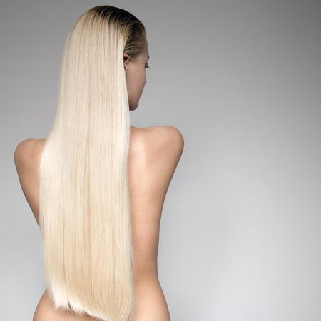 cabello rubio: Retrato de una mujer joven hermosa rubia con el pelo largo recto. Vista trasera