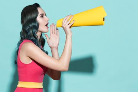 美しい少女は、青い背景に紙スピーカーで話します。