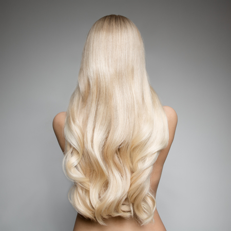 Portrait Of Beautiful Young Blond Woman With Long Wavy Hair. Back view