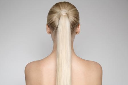 Portret van een mooie jonge blonde vrouw met paardenstaart kapsel. Achteraanzicht