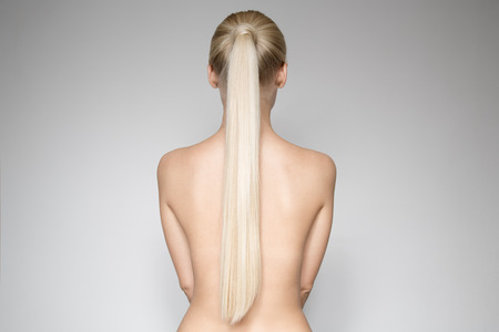 Portrait Of A Beautiful Young Blond Woman With Ponytail Hairstуle. Back view