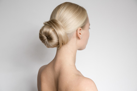 rear view: Portrait Of Beautiful Young Blond Woman With Bun Hairstуle. Back View Stock Photo