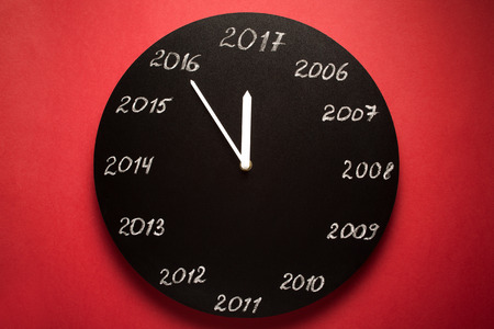 transience: Concept of clock on the eve of 2017. Red background. Stock Photo