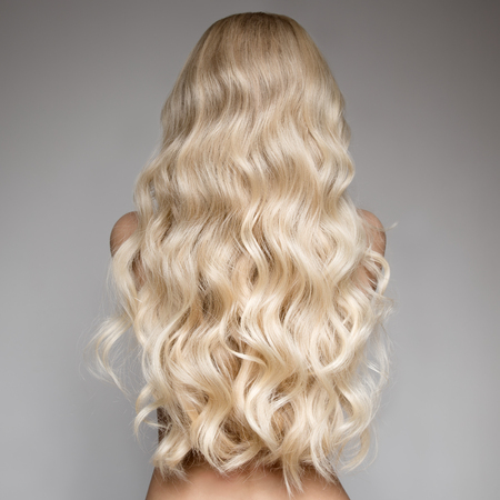 Ritratto Di Bella giovane donna bionda con lunghi capelli ondulati. Vista posteriore Archivio Fotografico - 66734665