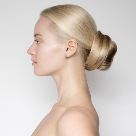 Portrait Of Beautiful Young Blond Woman With Bun Hairstуle. Side View Stock Photo