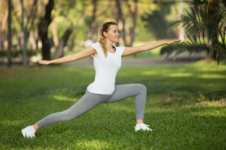 Young woman stretching in city park