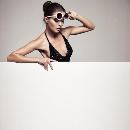 Beautiful woman in black bikini holding big empty white billboard. Stock Photo