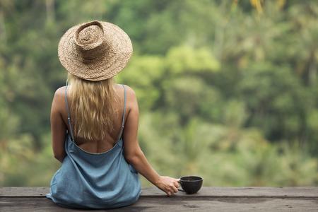농촌 여자 siting 및 정글 숲에 커피 한잔. 후면보기.