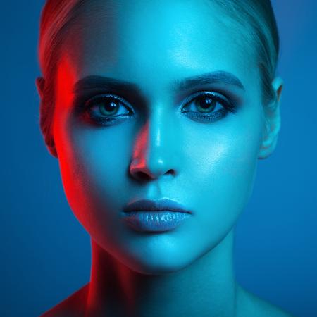 Mode kunst portret van mooie vrouw gezicht. Rode en blauwe lichte kleur. Stockfoto