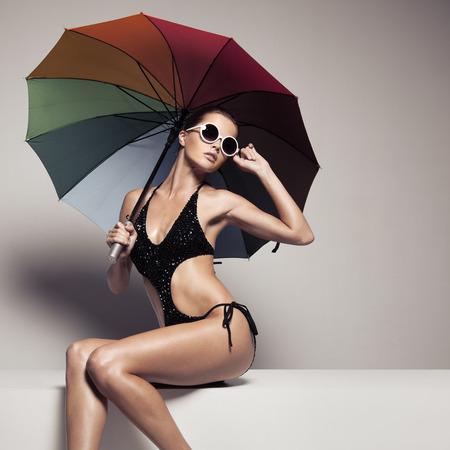 Mooie vrouw in stijlvolle zwarte badkleding en zonnebril met kleurrijke paraplu. Perfect slank gelooid lichaam. Stockfoto