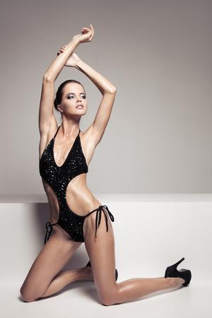 mujeres eroticas: Retrato de mujer hermosa elegante con encanto componen en traje de baño negro con estilo. Carrocería perfecta morena delgado. Foto de archivo