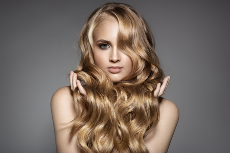 Portrait Of A Beautiful Young Blond Woman With Long Wavy Hair Фото со стока