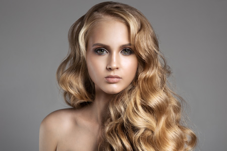 capelli biondi: Portrait Of A Beautiful Young Blond Woman With Long Wavy Hair Archivio Fotografico