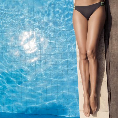 Beautiful woman legs sunbathing near swimming pool. Фото со стока