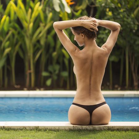 Jonge vrouw zonnen bij het zwembad. Terug te bekijken.