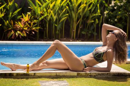 Young slim beautiful woman in bikini sunbathing near swimming pool. photo