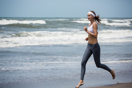 Young sporty woman running on the beach. photo