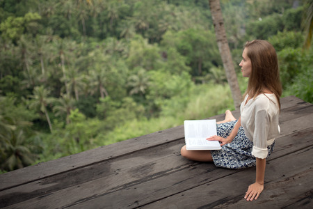 Young woman relaxing on balcony and reading book. photo
