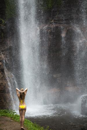 Beautiful woman in red bikini and waterfall. photo