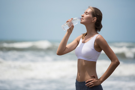 Young sporty woman drinking water after training on the beach. photo