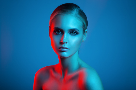 Fashion art portrait of beautiful woman face. Red and blue light color. Banque d'images