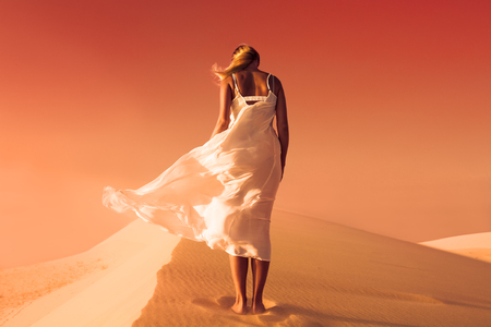 unrealistic: Woman in fluttering dress. Desert and sand dunes. Red sky. Mars.