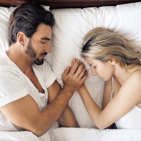 魅力的なカップルの寝室で眠っています。