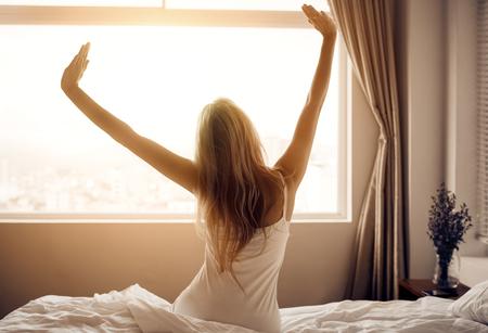 Une jeune femme se réveille dans la chambre. Banque d'images