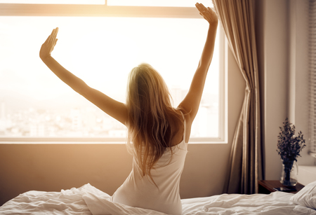 Young woman wake up in bedroom. Stock Photo