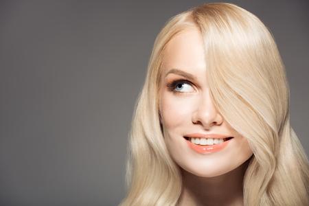 salud sexual: Retrato de la mujer joven hermosa rubia con pelo largo y ondulado.