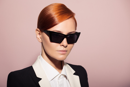 Fashion portrait of serious woman dressed as a secret agent or spy. Pink background. photo