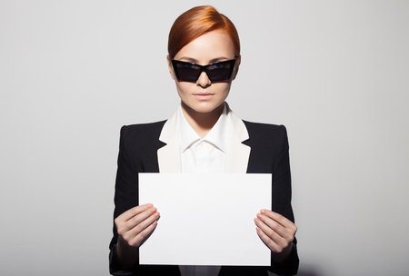 Fashion portrait of serious woman dressed as a secret agent or spy. Holding empty blank in hand. photo
