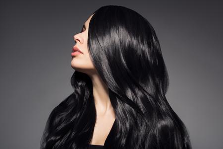 長いウェーブのかかった髪を持つ美しい若いブルネットの女性の肖像画。 写真素材