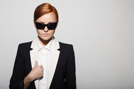 Fashion portrait of serious woman dressed as a secret agent or spy. Gray background. photo