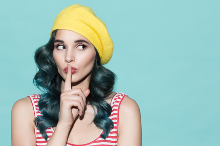 Beautiful woman in a yellow beret makes a gesture of silence. On a blue background. Stock Photo