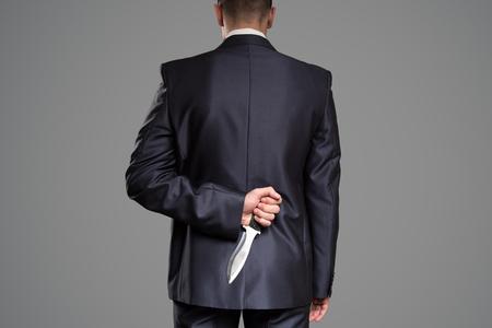 Man hide knife behind back. Killer concept. Stock Photo