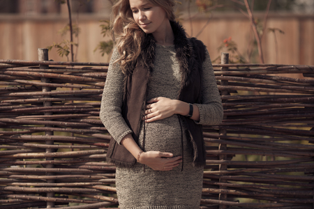 Attractive pregnant woman in cozy clothes at countryside photo
