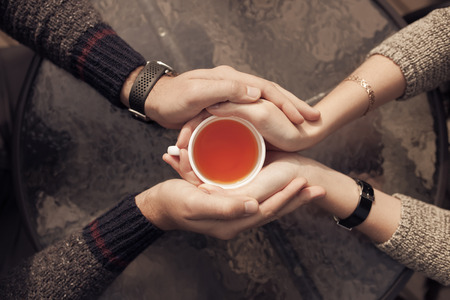 Couple hands holding cup of tea. Top view. photo