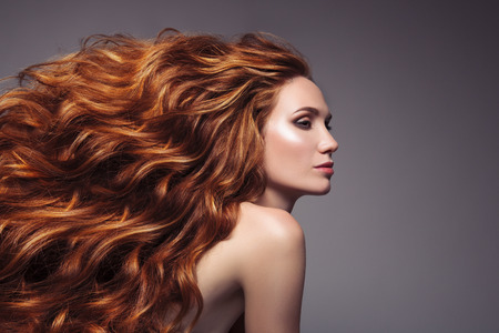 長い巻き毛の美しい生姜髪の女性の肖像画。