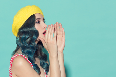 노란색 베레모에서 아름 다운 여자는 그녀의 손에서 스피커를 만든다. 파란색 배경에.