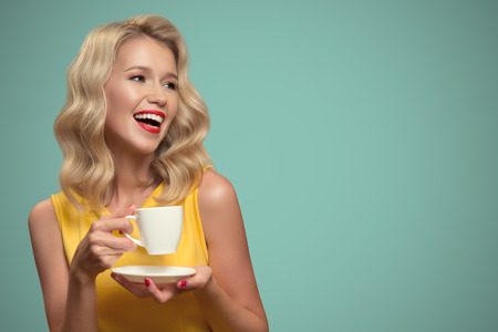 Pop art portrait of beautiful woman drinking coffee on blue background.