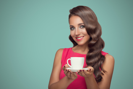 Portrait of beautiful woman drinking coffee on blue background.