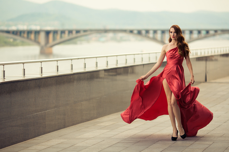 satin dress: Beautiful woman in red fluttering dress. Urban background. Stock Photo